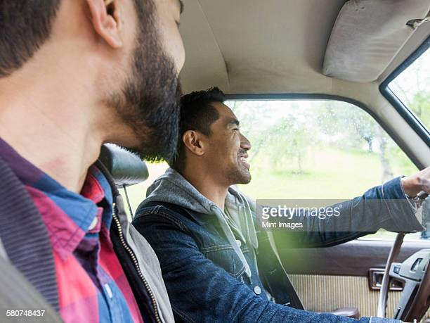Two young men in a car, driver and passenger, smiling.