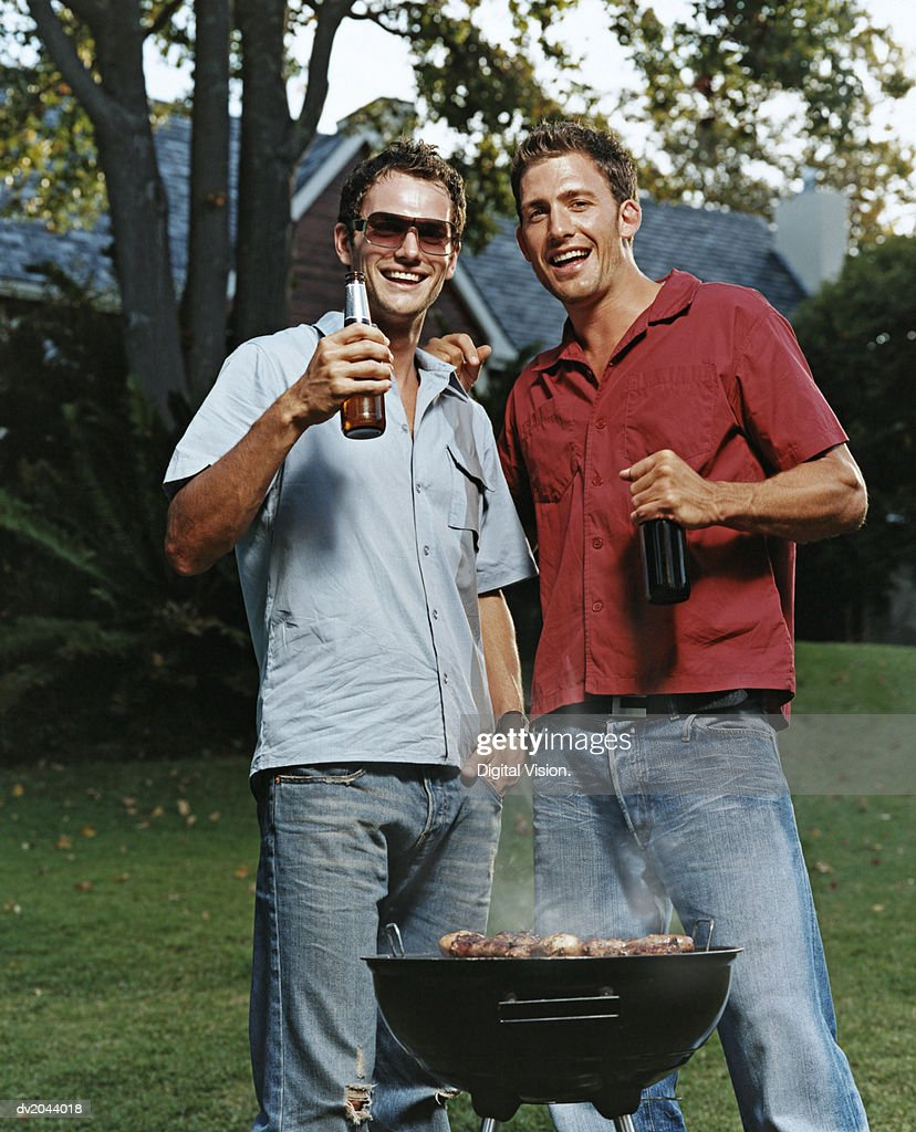 Two Young Men in a Garden With a Beer and Barbeque : Stock Photo