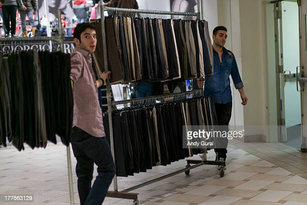 Two young men in a shopping mall move racks of dress trousers for men.