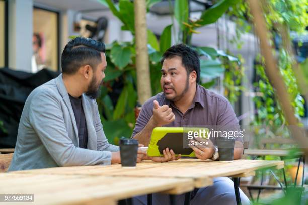 Two young men in an informal business meeting
