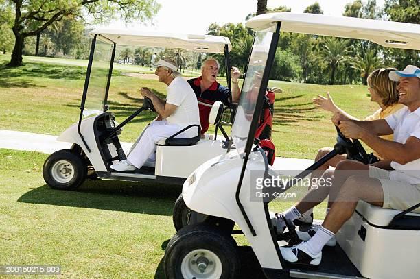 Two young men in golf cart beside mature men in golf cart