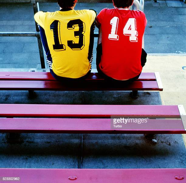 two young men in soccer jerseys on bench - fußballtrikot stock-fotos und bilder