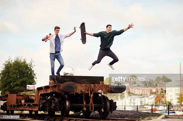 Two young men jumping from trailer on train track, Bristol, UK