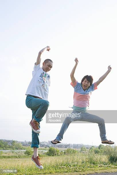 Two young men jumping on a river bank