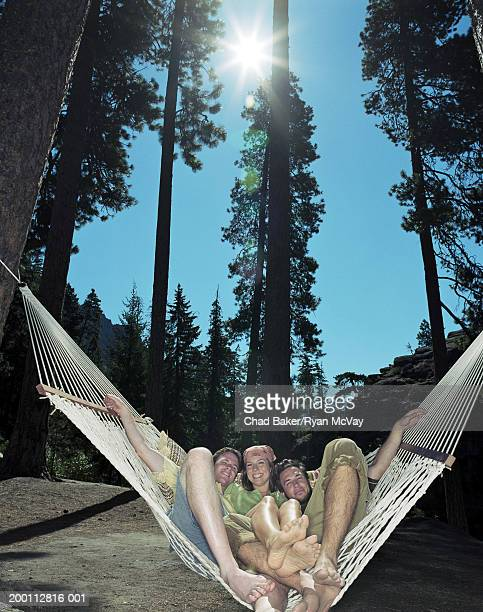 two young men lying in hammock with young woman, portrait - 18 19 years stock pictures, royalty-free photos & images