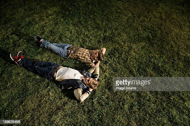Two young men lying on grass at night, high angle