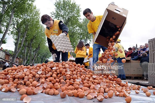 Two young men members of the brotherhood of the Bessieres' giant Easter omelette throw eggshells as they take part in the preparation of a giant...