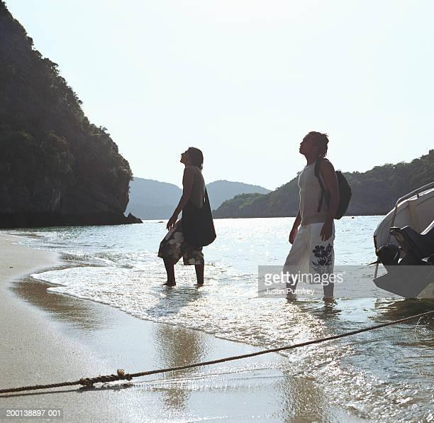two young men on beach, facing inland, surf washing around feet - vertäut stock-fotos und bilder