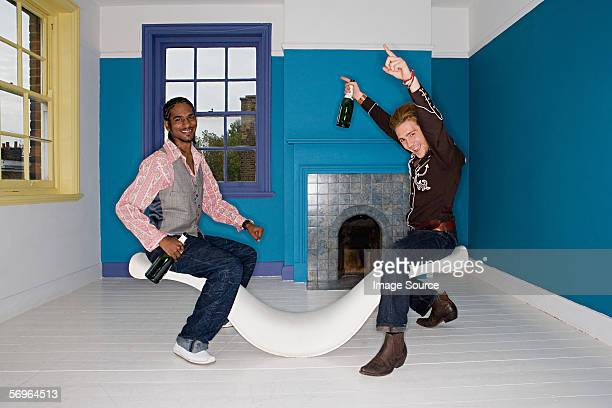 Two young men on seesaw chair