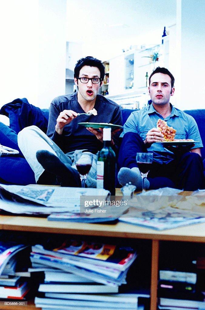 Two Young Men On Sofa Eating Take Away Food Stock Photo