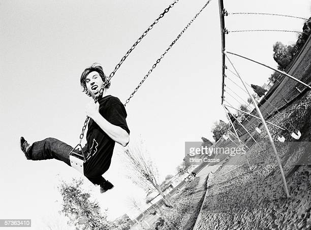 Two young men on swings in playground