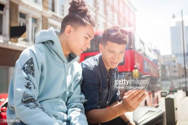 Two young men outdoors, looking at smartphone