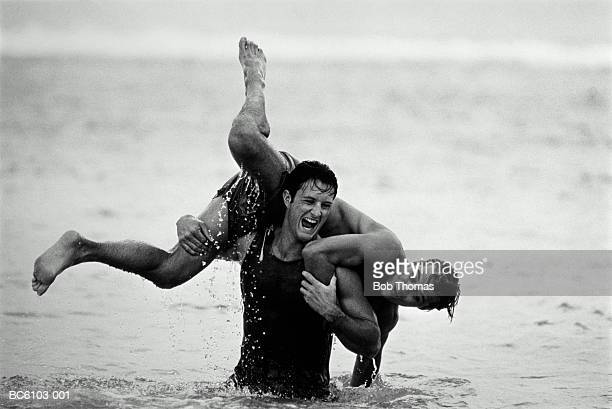 two young men playfully throwing each other about in sea (b&w) - only young men stock pictures, royalty-free photos & images
