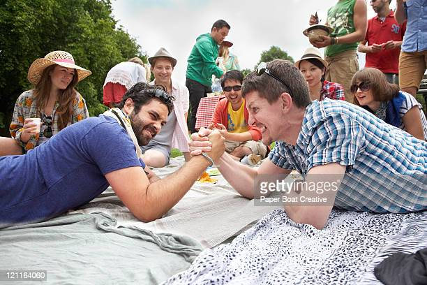 Two young men playing arm wrestle in the park