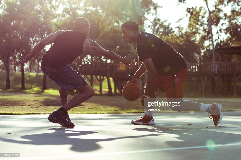 Two young men playing basketball in the park at sunset : Stock Photo