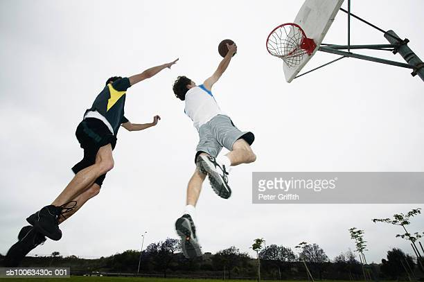 Two young men playing basketball, low angle view