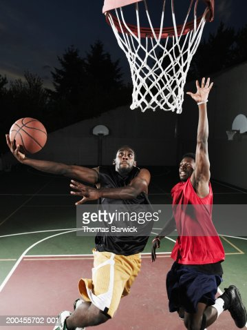 Two Young Men Playing Basketball On Outdoor Basketball ...