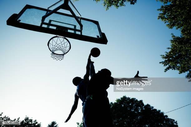 Zwei junge Männer spielen Basketball auf Freiplatz