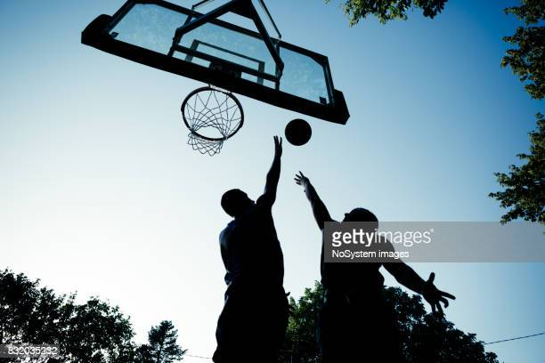 2 つの若い男性が屋外コートでバスケット ボールをプレー - デイフェンス ストックフォトと画像