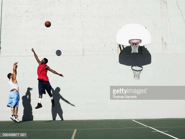 two young men playing basketball outdoors, side view - shooting baskets stock photos and pictures