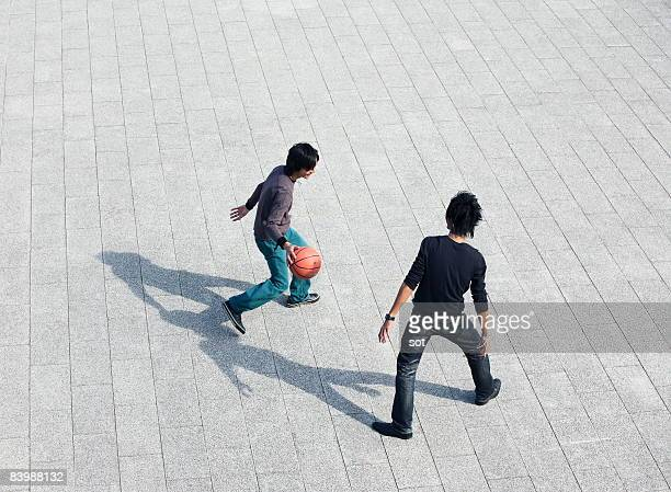 Two young men playing basketball paving stone