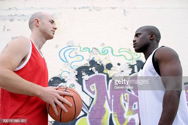 two young men playing basketball, staring at one another, side view - スポーツユニフォーム ストックフォトと画像