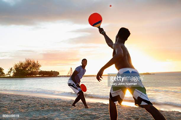 Two young men playing beach tennis at sun