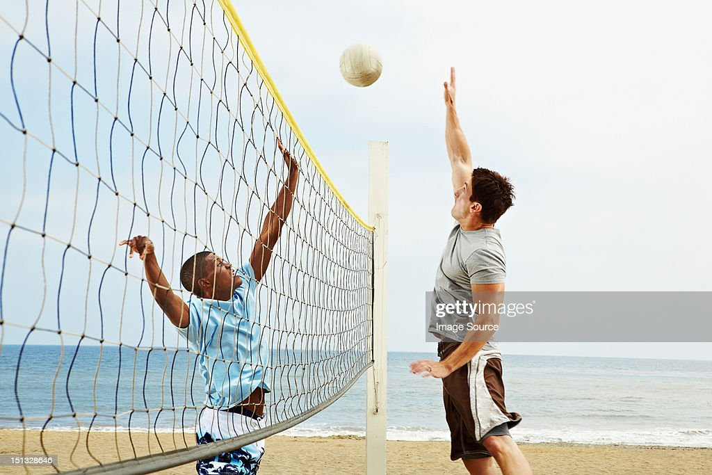 Two young men playing beach volleyball : Stock Photo