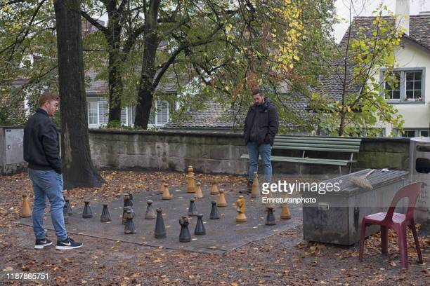 two young men playing chess outdoors,zurich. - emreturanphoto ストックフォトと画像