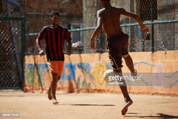 two young men playing football on a dirt court - favela stock pictures, royalty-free photos & images
