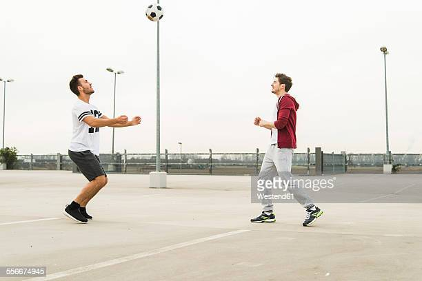 Two young men playing soccer on parking level
