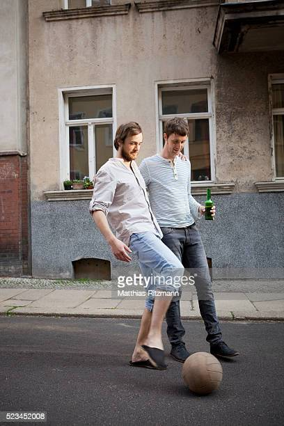 Two young men playing soccer on street