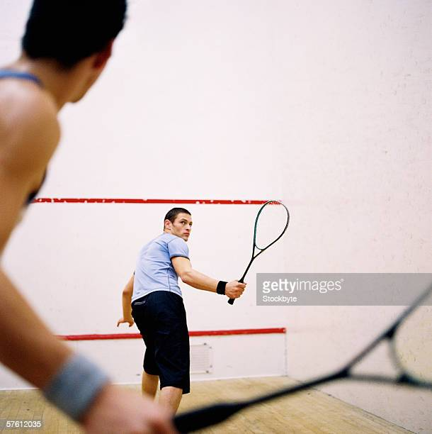 Two young men playing squash
