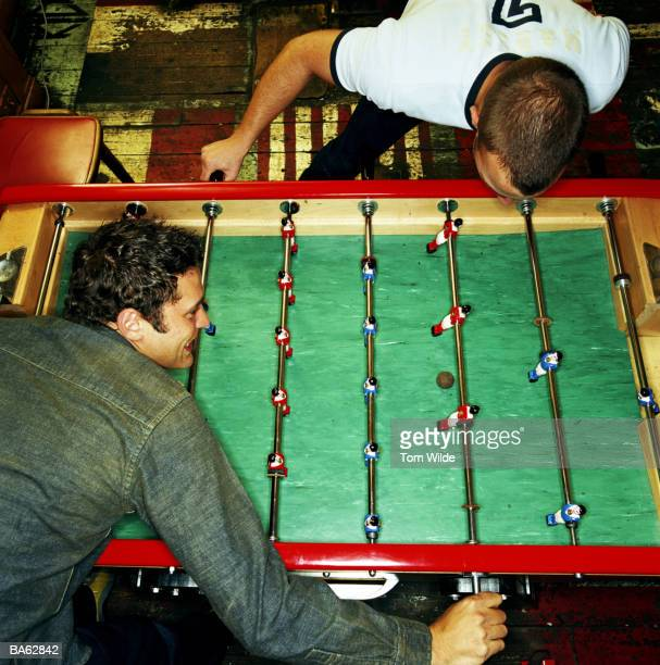 Two young men playing table football, elevated view