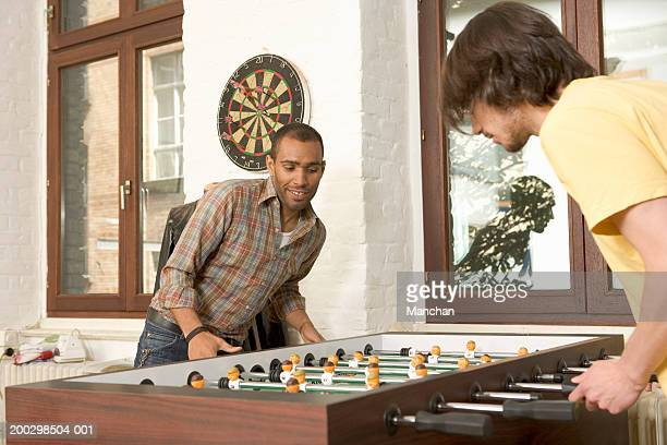 Two young men playing table football