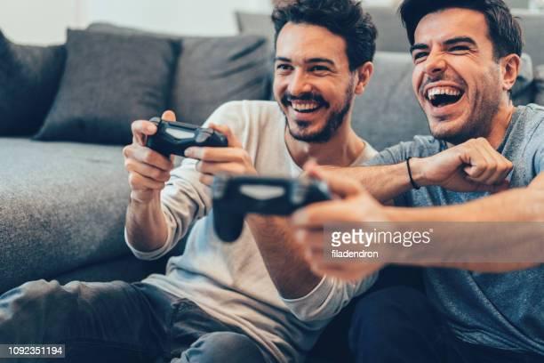 二人の若者がビデオ ゲームをプレイ - テレビゲーム ストックフォトと画像
