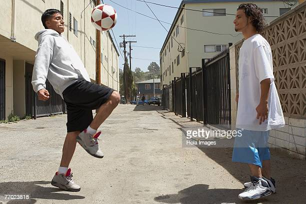 Two young men playing with a soccer ball on the street