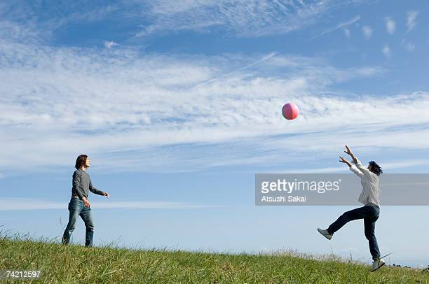 Two young men playing with beach ball