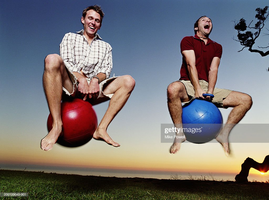Two young men playing with bounce and hop balls : Stock Photo