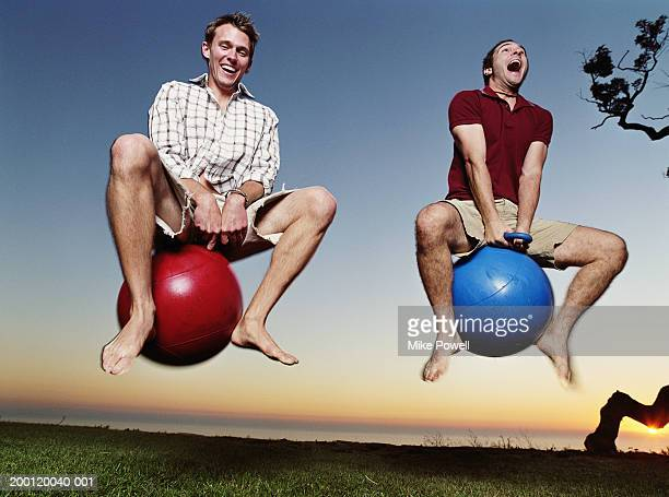 two young men playing with bounce and hop balls - young at heart stock pictures, royalty-free photos & images