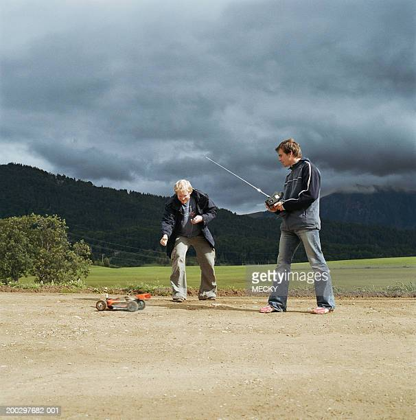 Two young men playing with radio controlled car, outdoors