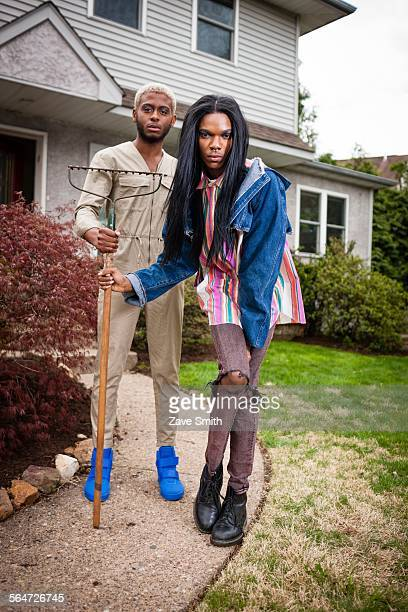 two young men posing in front yard with rake - transgender man stock photos and pictures