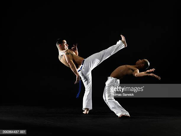 Two young men practicing capoeira, side view