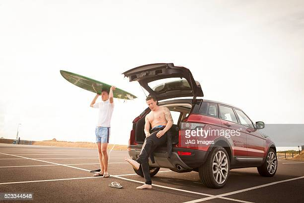 Two young men prepare to go surfing