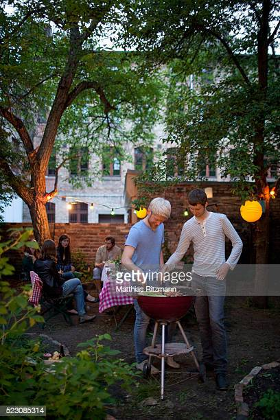 Two young men preparing food on barbecue grill