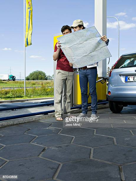 two young men reading map at petrol station