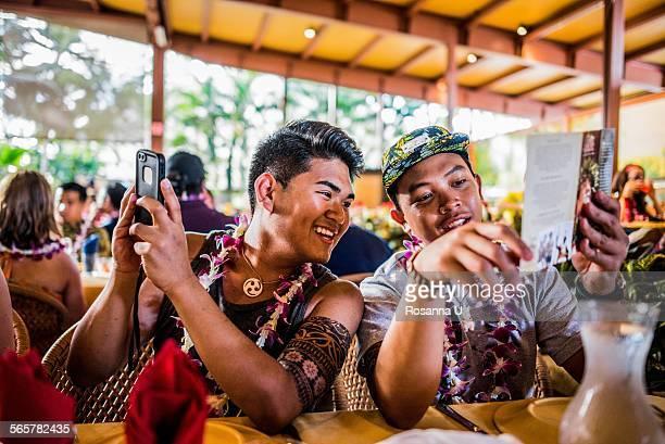 Two young men reading menu in Polynesian Cultural Centre, Hawaii, USA