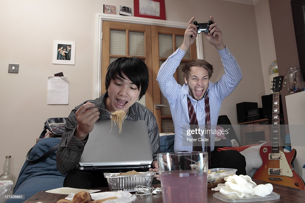 two young men relaxing after work in shared house : Stock Photo