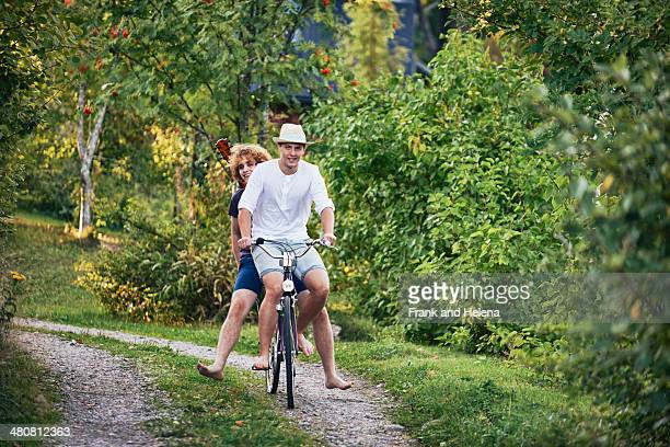 Two young men riding bicycle barefoot, Gavle, Sweden