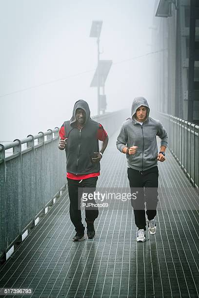 two young men running on iron bridge - pjphoto69 stock pictures, royalty-free photos & images